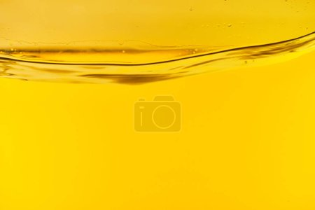 Photo pour Eau douce claire ondulée sur le fond lumineux jaune - image libre de droit