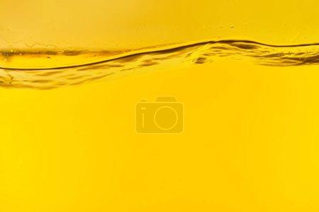 Foto de Agua dulce clara ondulada sobre fondo amarillo brillante - Imagen libre de derechos