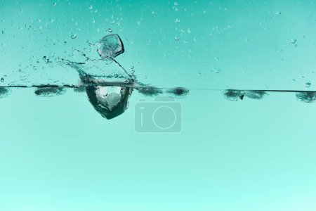Photo for Transparent ice cubes falling in water with splash on turquoise background - Royalty Free Image