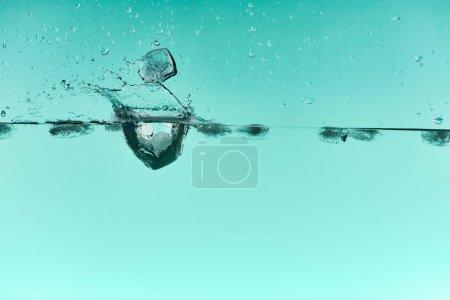Photo pour Glaçons transparents tombant dans l'eau avec l'éclaboussure sur le fond turquoise - image libre de droit
