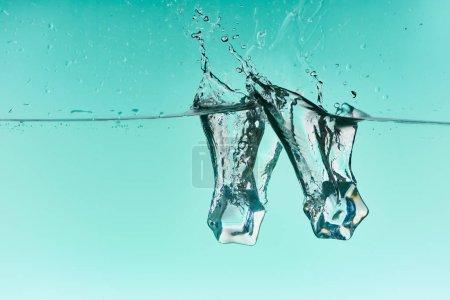 Photo pour Glaçons tombant dans l'eau avec l'éclaboussure sur le fond turquoise - image libre de droit