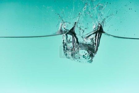 Photo pour Glaçons transparents tombant dans l'eau avec éclaboussure sur fond turquoise - image libre de droit