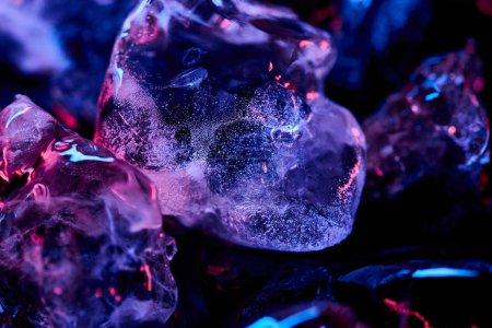 Foto de Vista de cerca de cubos de hielo transparentes con iluminación púrpura aislada en negro - Imagen libre de derechos