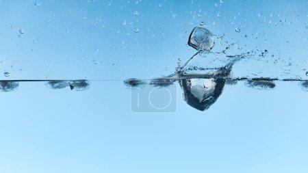 Photo pour L'eau transparente avec les glaçons tombants et éclaboussent sur le fond bleu - image libre de droit