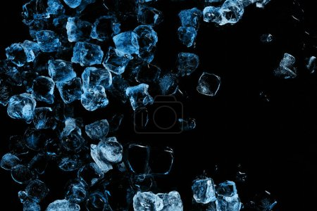 Photo for Top view of frozen ice cubes with blue light isolated on black - Royalty Free Image