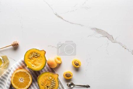 Foto de Vista superior de la toalla a rayas con mitades de calabaza, albaricoques y jarra de naranja cerca de la miel en la superficie de mármol - Imagen libre de derechos