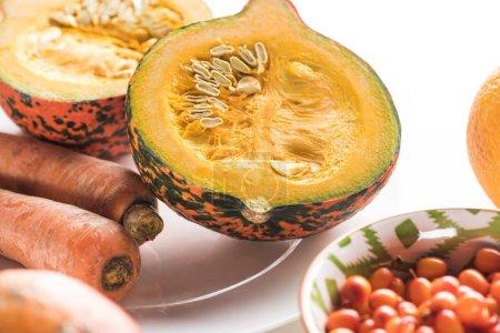 Photo pour Moitiés de citrouille et carottes sur l'assiette sur la surface de marbre - image libre de droit