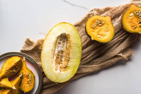 Photo pour Vue de dessus de la moitié de melon et assiette avec citrouille sur toile - image libre de droit