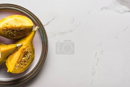 Photo for Top view of plate with pumpkin quarters on marble table - Royalty Free Image