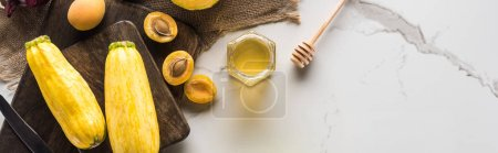 Photo for Panoramic shot of cutting boards with zucchini, apricots and honey on marble surface - Royalty Free Image