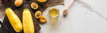 Photo pour Plan panoramique de planches à découper avec courgettes, abricots et miel sur la surface du marbre - image libre de droit