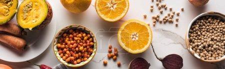 Photo pour Plan panoramique de bols avec des pois chiches et des baies près des fruits et légumes crus sur la surface du marbre - image libre de droit