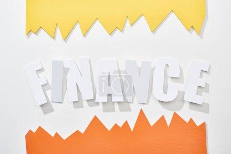Foto de Vista superior de la inscripción financiera con gráficos estadísticos naranjas y amarillos sobre fondo blanco - Imagen libre de derechos