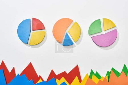 top view of multicolor statistic graphs and pie charts on white background