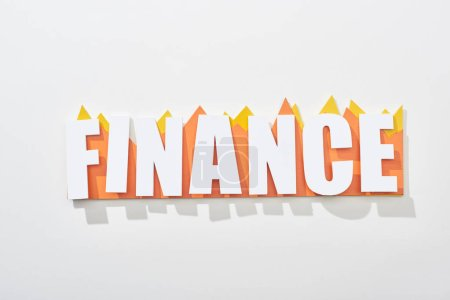 Photo for Top view of finance inscription above orange and yellow statistic graphs on white background - Royalty Free Image