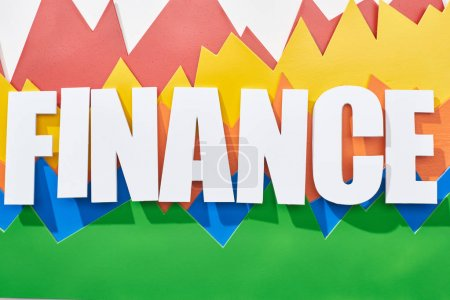 Foto de Vista superior de la inscripción de finanzas por encima de gráficos estadísticos de color sobre fondo blanco - Imagen libre de derechos