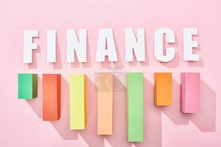Foto de Vista superior de la inscripción financiera con gráfico de bloque de color sobre fondo rosa - Imagen libre de derechos