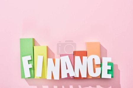 Photo pour Vue supérieure de l'inscription de finances au-dessus du graphique de bloc de couleur sur le fond rose - image libre de droit