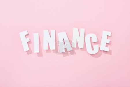 Photo for Top view of white finance word with shadows on pink background - Royalty Free Image