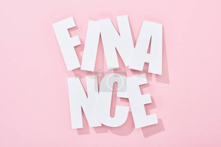 Photo for Top view of white finance inscription with shadow on pink background - Royalty Free Image