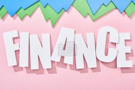 Photo pour Vue du haut de l'inscription de la finance avec des graphiques statistiques verts et bleus sur fond rose - image libre de droit