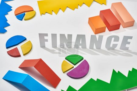 Photo for Finance inscription near multicolor blocks and pie charts with shadow on white background - Royalty Free Image