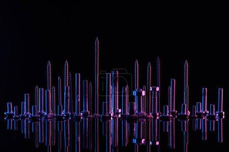 Photo pour Diverses vis métalliques violettes isolées sur le noir - image libre de droit