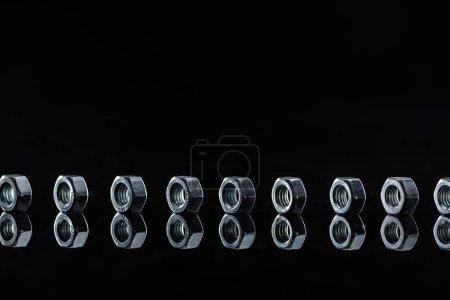 Photo pour Ligne horizontale de noix en métal isolées sur le noir - image libre de droit