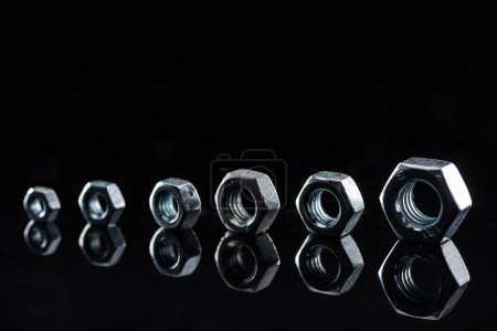 Photo for Metal nuts of different sizes isolated on black - Royalty Free Image