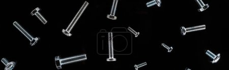 Photo for Panoramic shot of scattered metal bolts pattern isolated on black - Royalty Free Image