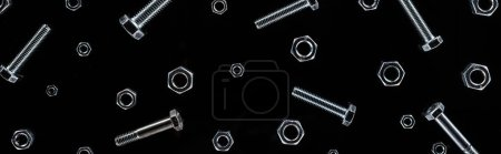 Photo for Panoramic shot of scattered metal bolts and nuts pattern isolated on black - Royalty Free Image