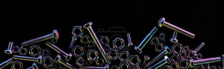 panoramic shot of scattered steel nuts and bolts isolated on black with copy space