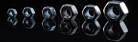 Photo for Panoramic shot of shiny steel nuts row isolated on black - Royalty Free Image