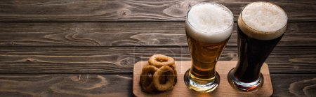 Photo for Panoramic shot of glasses of dark and light beer with foam near fried onion rings on wooden table - Royalty Free Image
