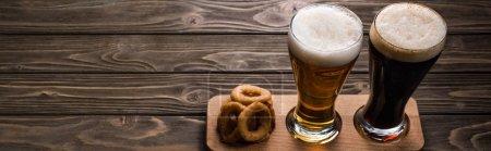 Photo pour Coup panoramique des glaces de bière foncée et légère avec la mousse près des anneaux frits d'oignon sur la table en bois - image libre de droit