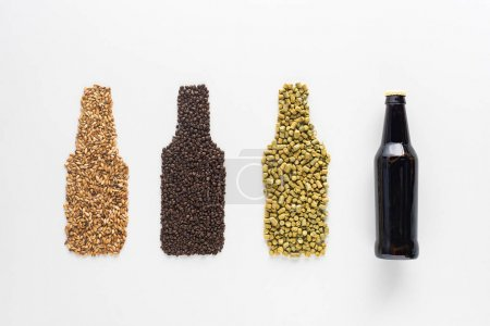 top view of bottle of dark beer near wheat, coffee grains and pressed hop isolated on white