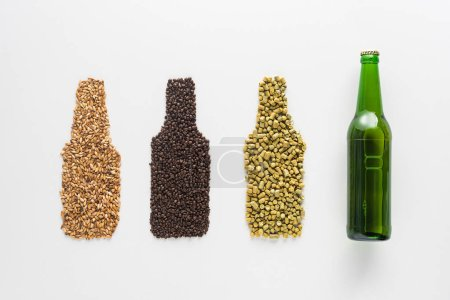 top view of bottle of beer near wheat, coffee grains and pressed hop isolated on white