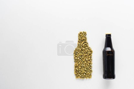 top view of bottle of dark beer near pressed hop isolated on white