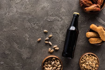 Photo for Top view of bottle of dark beer near bowls with nuts and chicken snacks on brown surface - Royalty Free Image