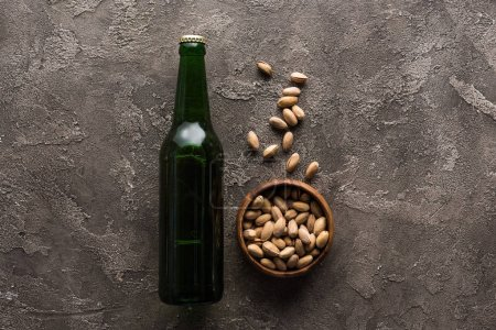 vue du dessus du bol avec des pistaches près de la bouteille verte de bière sur la surface brune