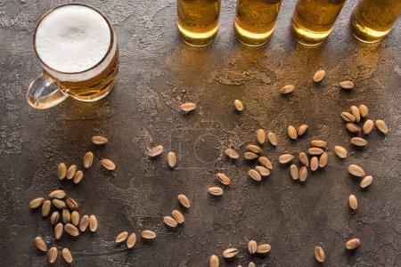 vue du dessus des bouteilles et tasse de bière légère près de pistaches dispersées sur la surface brune