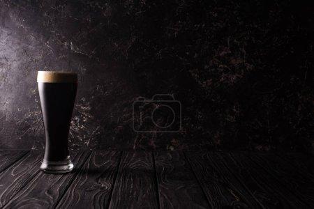 Foto de Vaso de cerveza oscura sobre mesa de madera con sombra - Imagen libre de derechos