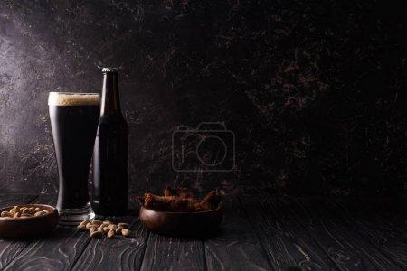 Photo pour Verre et bouteille de bière foncée près des cuvettes avec des pistaches et des ailes de poulet sur la table en bois - image libre de droit