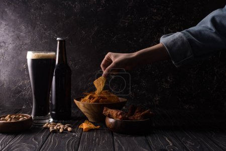 Photo for Cropped view of man taking piece of nachos near bottle and glass of beer and bowls with snacks on wooden table - Royalty Free Image