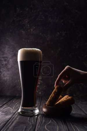 Photo for Cropped view of man taking piece of fried cheese near glass of beer on wooden table - Royalty Free Image