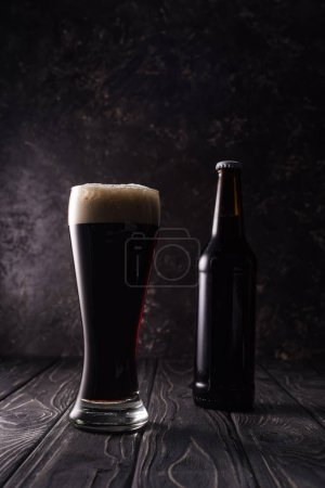 Photo for Bottle near glass of beer on wooden table - Royalty Free Image