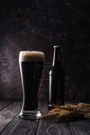 Photo for Bottle and glass of beer near wheat spikes on wooden table - Royalty Free Image