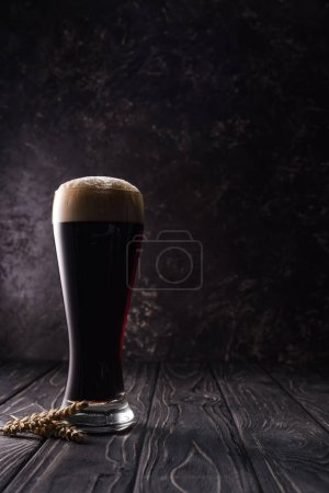 Photo for Glass of beer near wheat spikes on wooden table - Royalty Free Image