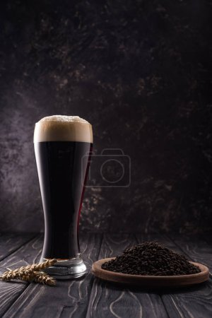 Photo for Glass of dark beer near wheat spikes and plate with coffee grains on wooden table - Royalty Free Image