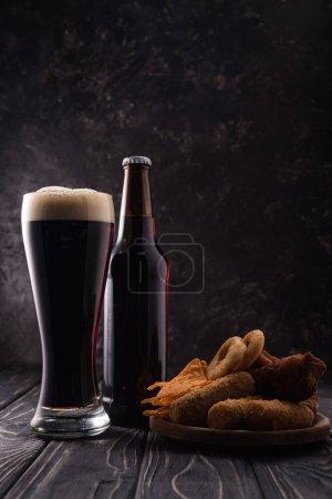 Photo pour Bouteille et verre de bière près de l'assiette avec des casse-croûte sur la table en bois - image libre de droit